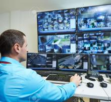 A security man watching CCTV footages of all the areas of building through monitor